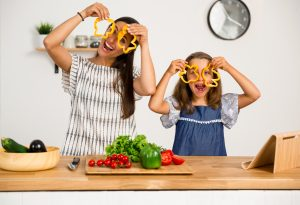 Shot of a mother and daughter having fun in the kitchen